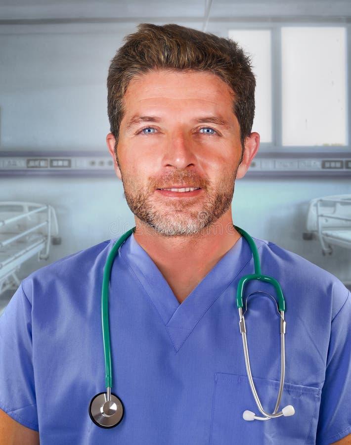 Ungt stiligt och säkert posera för medicindoktor som är gladlynt på blått, skurar och stetoskopet på hans hals som ler lyckligt s royaltyfria bilder