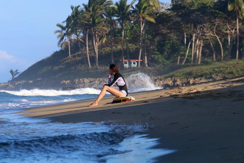 Ungt surfareflickasammanträde på stranden under solnedgång arkivbild