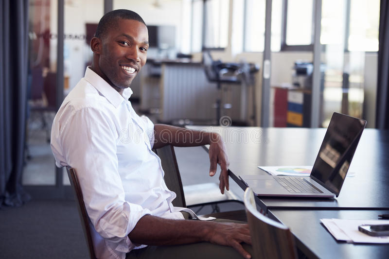 Ungt svart mansammanträde på skrivbordet i regeringsställning som ler till kameran arkivfoton