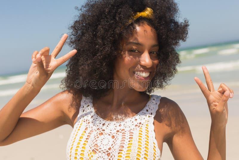 Ungt tecken för seger för afrikansk amerikankvinnavisning på stranden arkivfoto