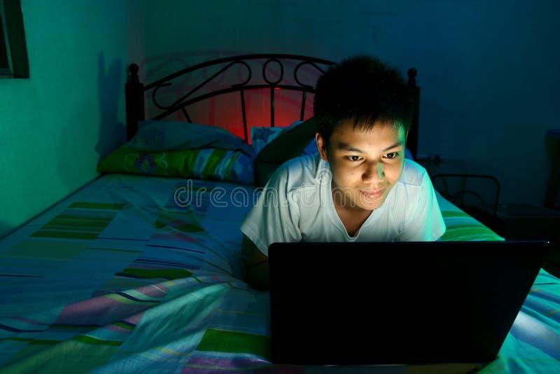 Ungt tonårigt framme av en bärbar datordator och på en säng royaltyfri fotografi