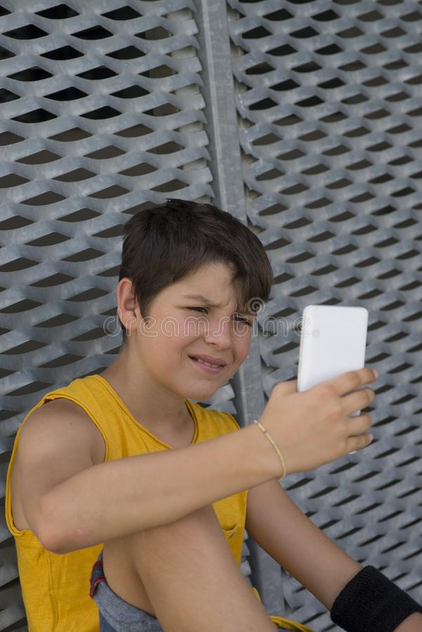Ungt tonårigt genom att använda hans telefon utomhus arkivfoto