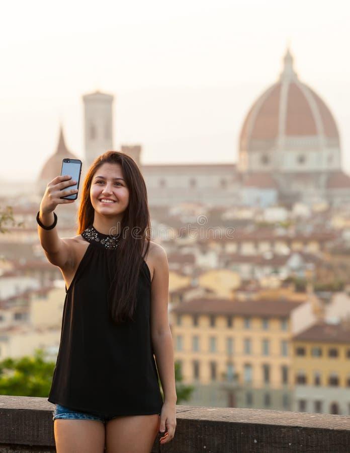 Ungt tonårigt tar en selfie på solnedgången i Florence royaltyfria foton