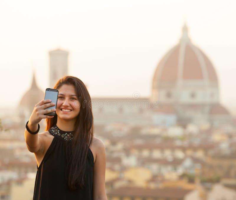 Ungt tonårigt tar en selfie på solnedgången i Florence arkivfoto