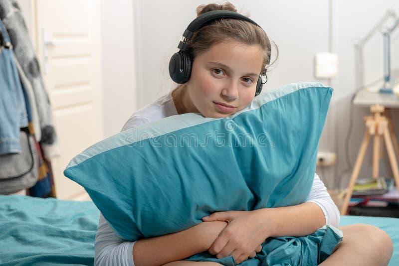Ungt tonårs- sammanträde på säng i sovrum att lyssna till musik med hea arkivfoto