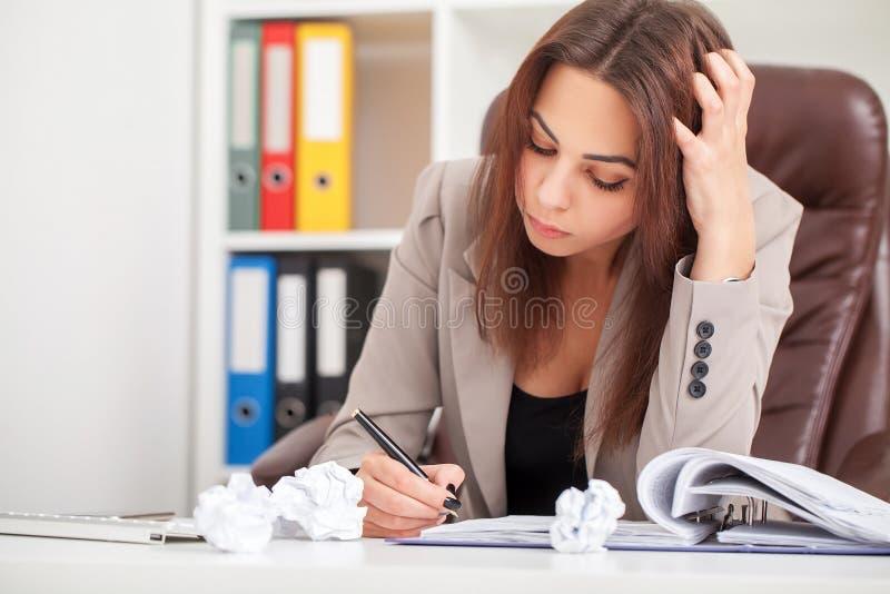 Ungt tråkigt affärskvinnasammanträde på tabellen med bärbara datorn och royaltyfri foto