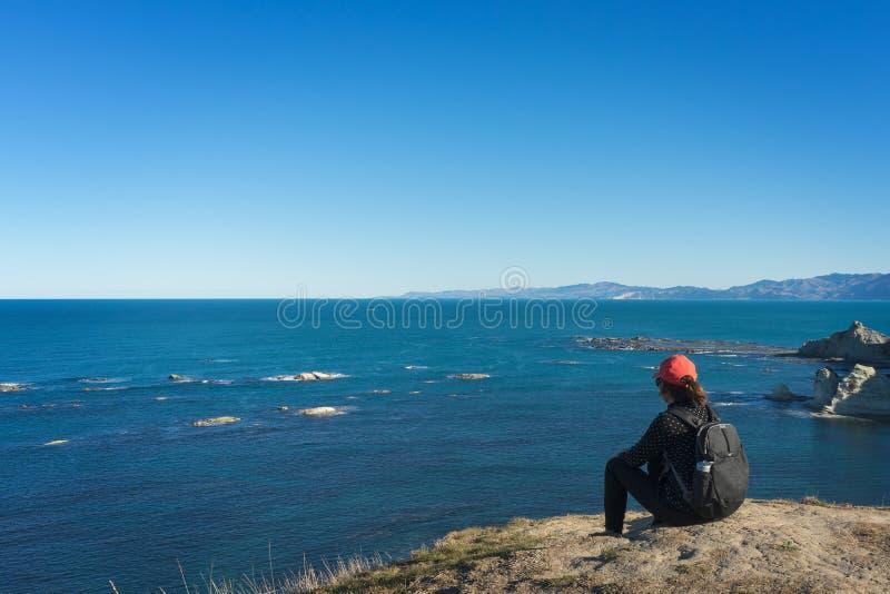Ungt turist- kvinnasammanträde på överkanten av klippan och att se a royaltyfri bild