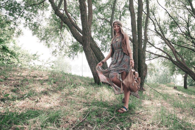 Ungt tycka om för hippiekvinna går i vårskog arkivfoto