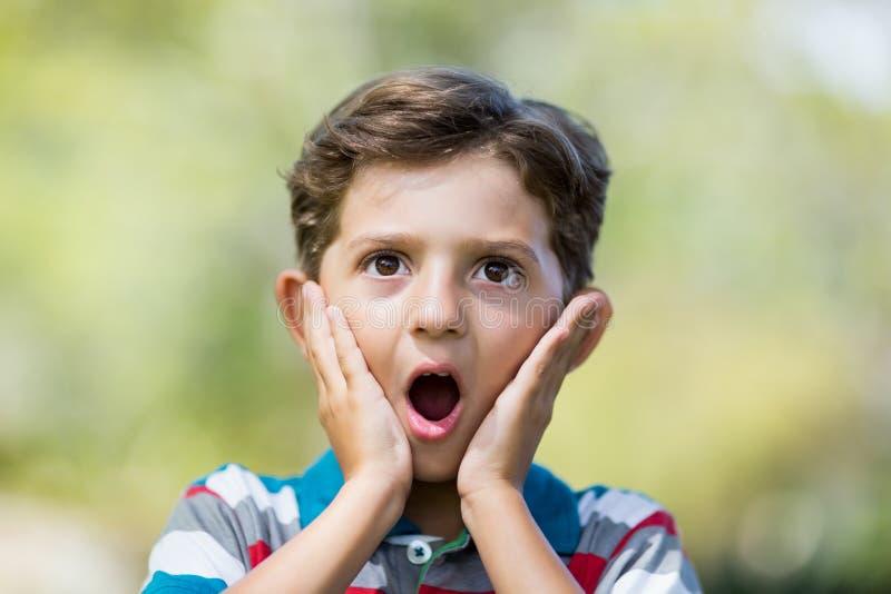 Ungt uttryck för pojkedanandeöverraskning, medan dra ut roliga framsidor royaltyfria bilder
