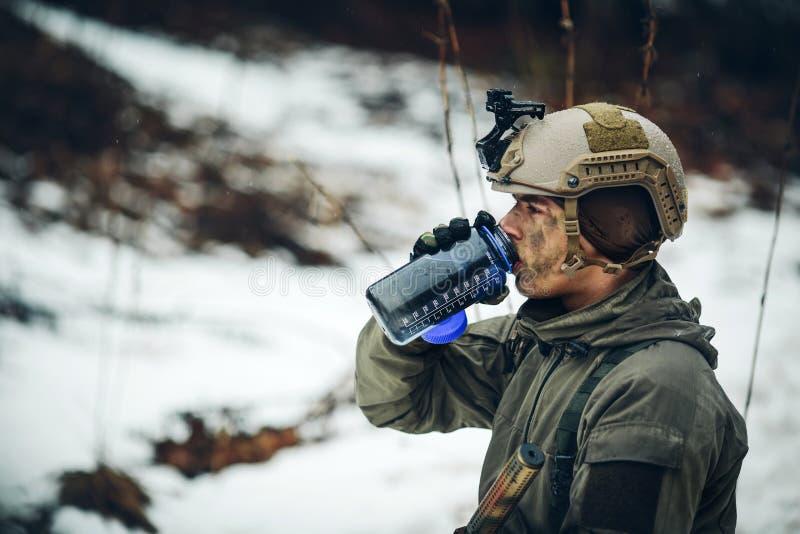 Ungt vatten för kommandosoldatmedlemdrink i skog arkivbild