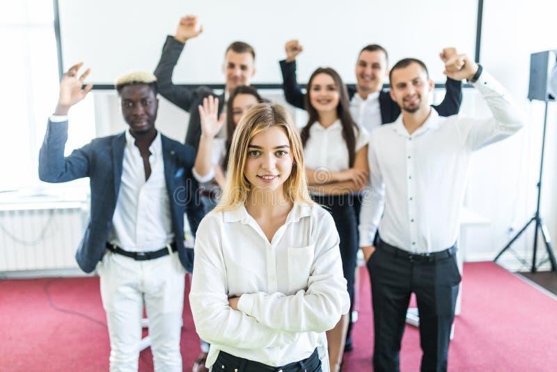 Ungt vitt kvinnligt utövande stående framme av kollegor med deras armar som lyfts upp lag för megafon för man för affärskaffelady arkivfoton