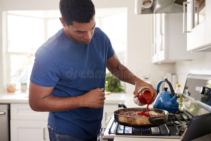 Ungt vuxet afrikansk amerikanmananseende i köket som lagar mat på hoben som tillfogar upp en sås till stekpannan, slut royaltyfri bild