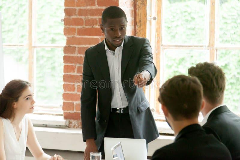 Unhöflicher afrikanischer Geschäftsmann, der Finger auf weißes Kollege duri zeigt stockfotos