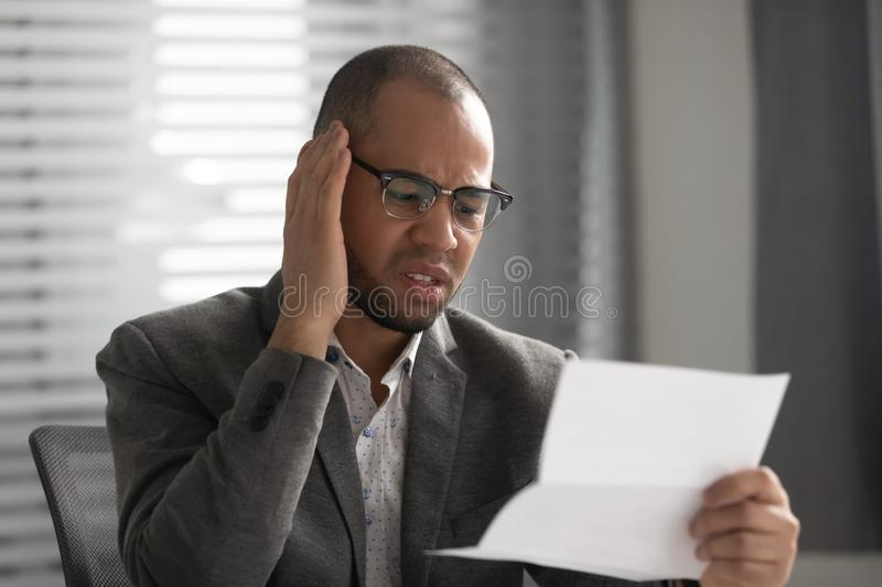Unhappy African American businessman reading document, receiving bad news royalty free stock image