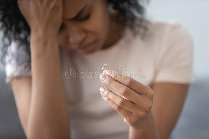 Unhappy African American woman holding wedding ring close up royalty free stock photo
