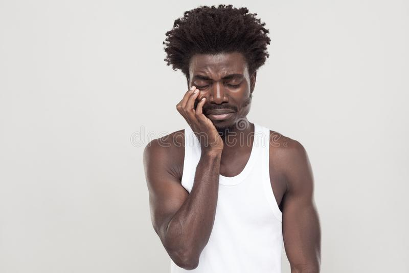 Unhappy afro man with souvarov mustache, cry and have depression. Closed eyes and cry. Unhappy afro man with souvarov mustache, cry and have depression. Indoor royalty free stock image