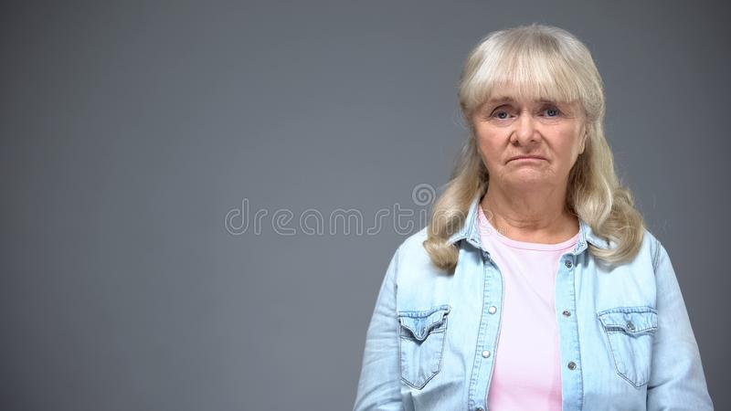 Unhappy aged female looking to camera, public dissatisfaction with state policy stock image
