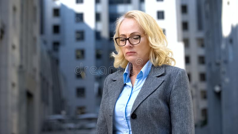 Unhappy aged lady in business suit looking depressed, pension age, unemployment stock photos