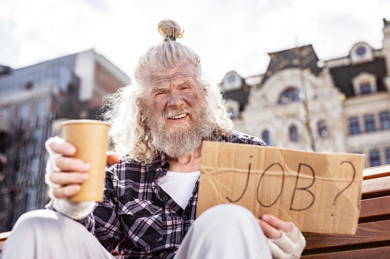 Unhappy aged man begging on the street. Financial crisis. Unhappy aged man begging on the street while being in the need for money royalty free stock photos