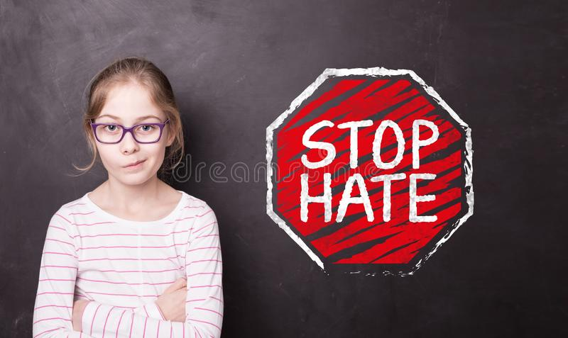 Angry child girl at the chalkboard with `STOP HATE` sign. Unhappy or angry blond child girl at the school chalkboard blackboard with `STOP HATE` sign. Education stock photos
