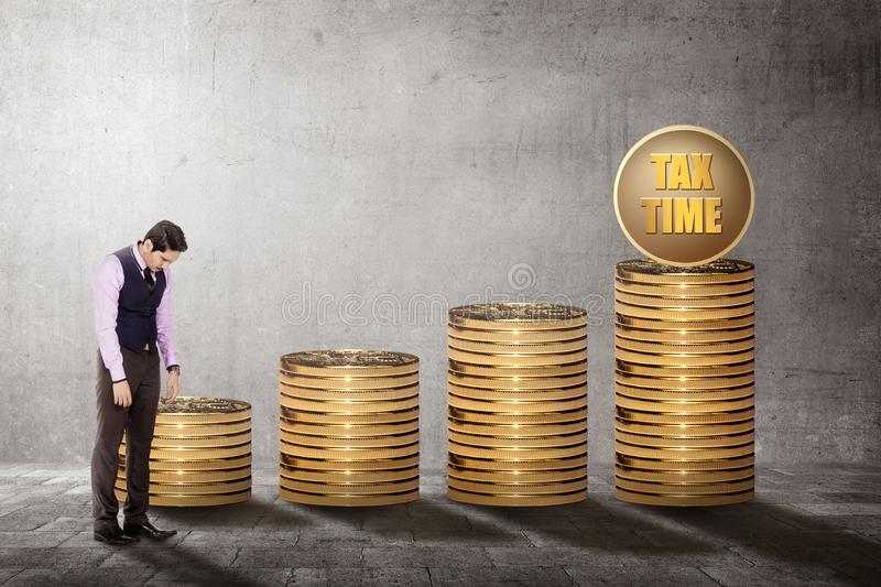 Unhappy asian businessman with coins stack and Tax time sign. Taxes concept royalty free stock photography