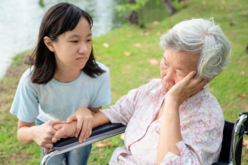 Unhappy asian child girl comfort upset offended senior grandmother,female teenager is stressed to trying to reconcile or. Compromise,elderly people looking away royalty free stock photos