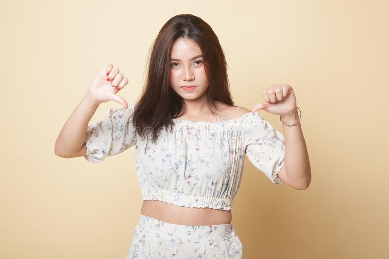 Unhappy Asian girl show thumbs down with both hands. Unhappy Asian girl show thumbs down with both hands on beige background royalty free stock image