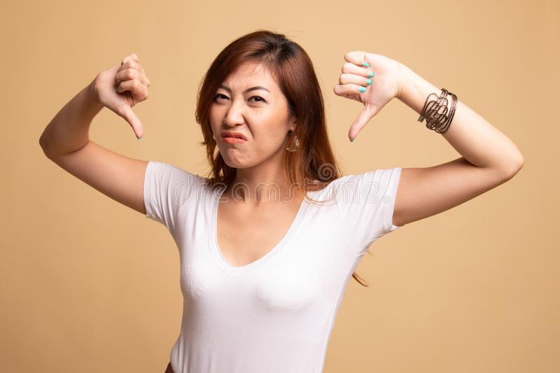 Unhappy Asian girl show thumbs down with both hands. On beige background stock image