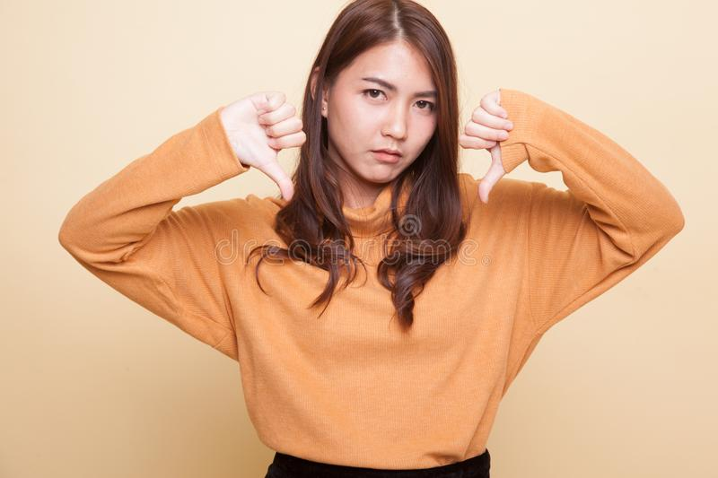 Unhappy Asian girl show thumbs down with both hands. Unhappy Asian girl show thumbs down with both hands on beige background royalty free stock photos