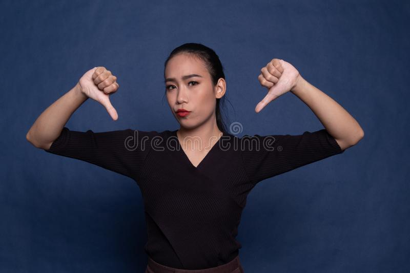 Unhappy Asian girl show thumbs down with both hands. On blue background royalty free stock photos