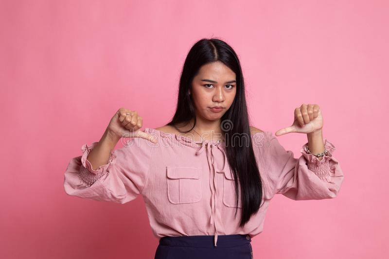 Unhappy Asian girl show thumbs down with both hands. On pink background royalty free stock photography