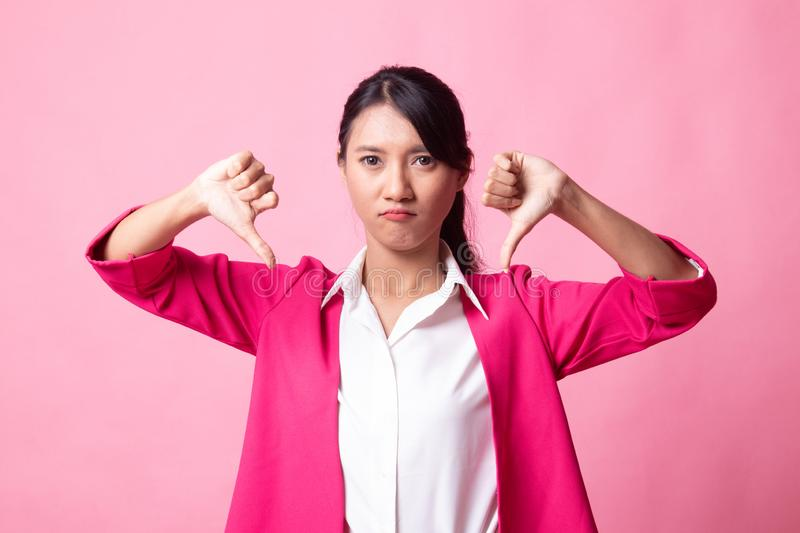 Unhappy Asian girl show thumbs down with both hands. On pink background royalty free stock photos