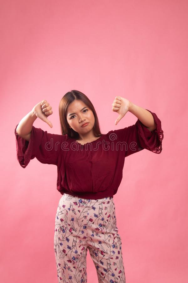 Unhappy Asian girl show thumbs down with both hands. On pink background stock photography