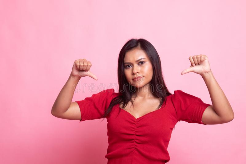 Unhappy Asian girl show thumbs down with both hands. On pink background stock photo