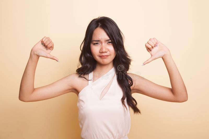 Unhappy Asian girl show thumbs down with both hands. Unhappy Asian girl show thumbs down with both hands on beige background royalty free stock images