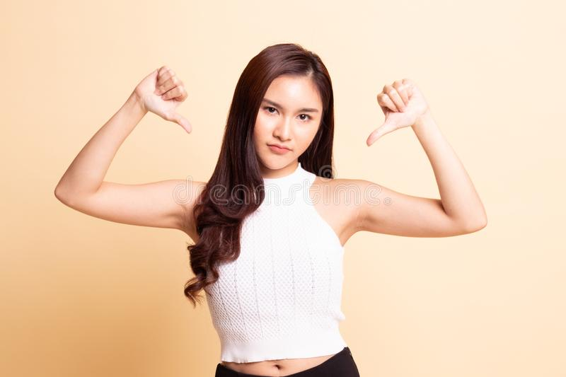 Unhappy Asian girl show thumbs down with both hands. On beige background royalty free stock photography