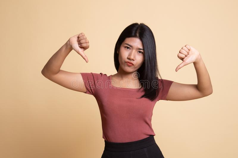 Unhappy Asian girl show thumbs down with both hands. On beige background stock photos
