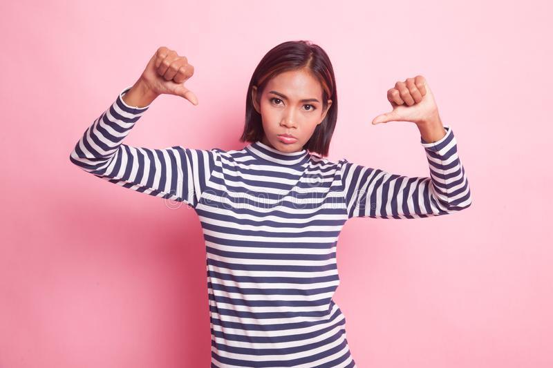Unhappy Asian girl show thumbs down with both hands. Unhappy Asian girl show thumbs down with both hands on pink background royalty free stock image