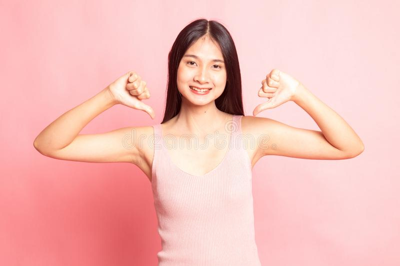 Unhappy Asian girl show thumbs down with both hands. On pink background stock image