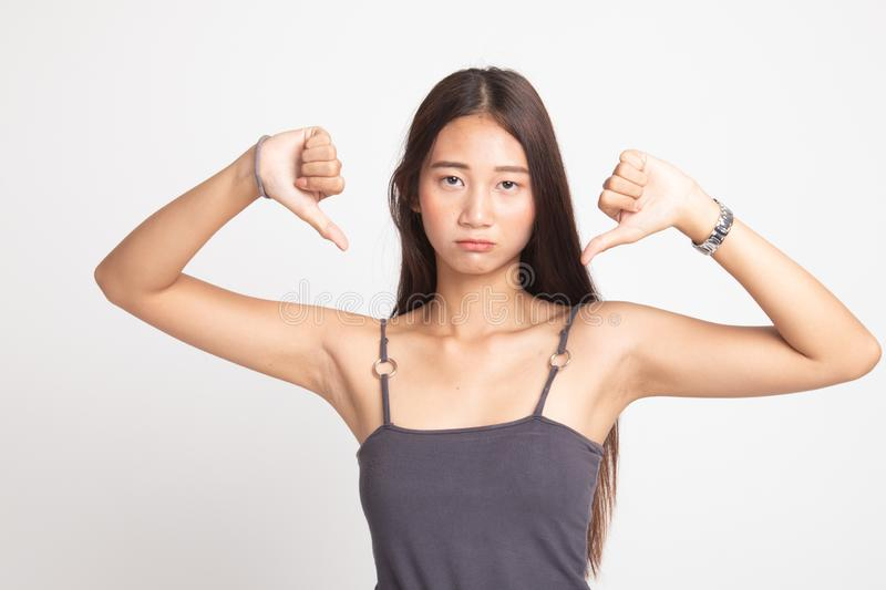 Unhappy Asian girl show thumbs down with both hands. On white background stock photo