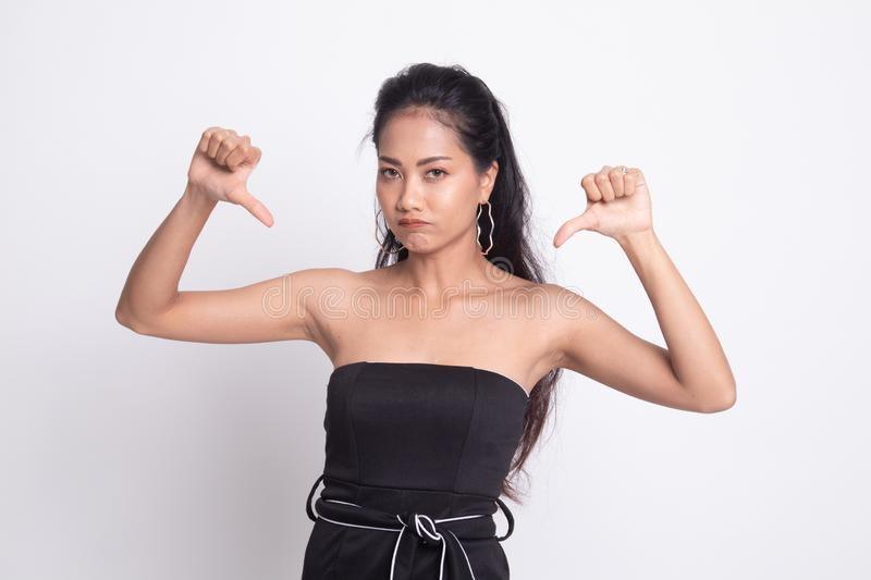 Unhappy Asian girl show thumbs down with both hands. On white background royalty free stock photo