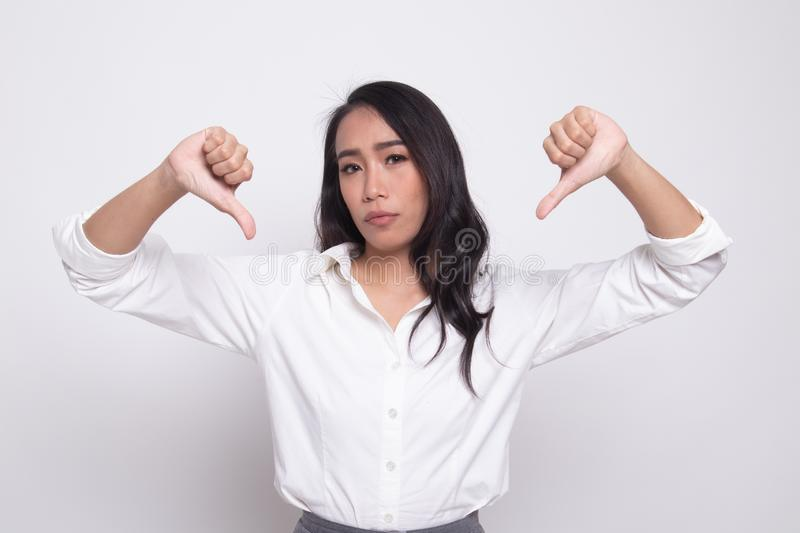 Unhappy Asian girl show thumbs down with both hands. On white background stock images