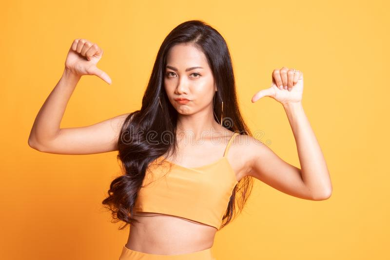 Unhappy Asian girl show thumbs down with both hands. On yellow background stock images