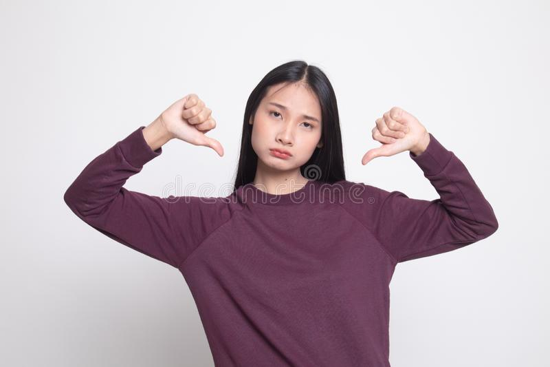 Unhappy Asian girl show thumbs down with both hands. On white background stock photos
