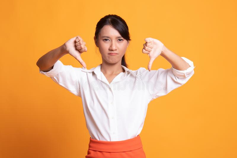 Unhappy Asian girl show thumbs down with both hands. On yellow background stock photography