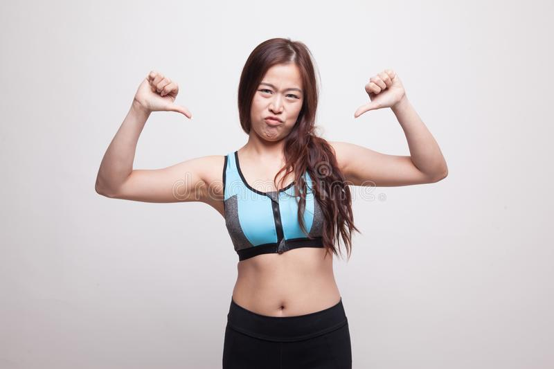 Unhappy Asian girl in sport dresses show thumbs down with both h. Ands on white background stock images