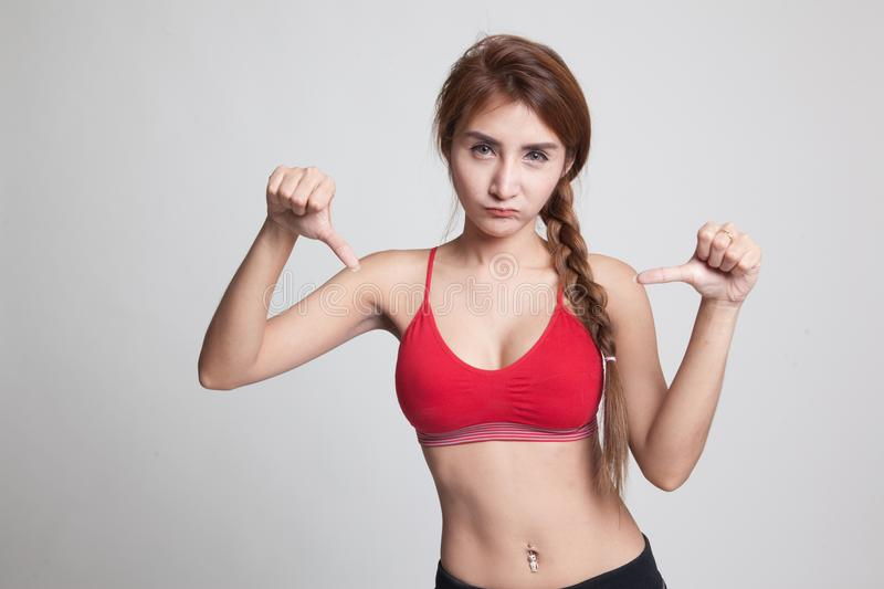 Unhappy Asian girl in sport dresses show thumbs down with both h. Ands on gray background royalty free stock photography