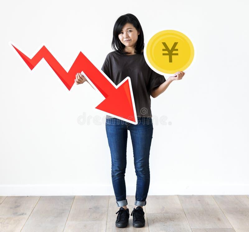 Unhappy Asian woman holding a Japanese Yen and financial decrease arrow stock photo