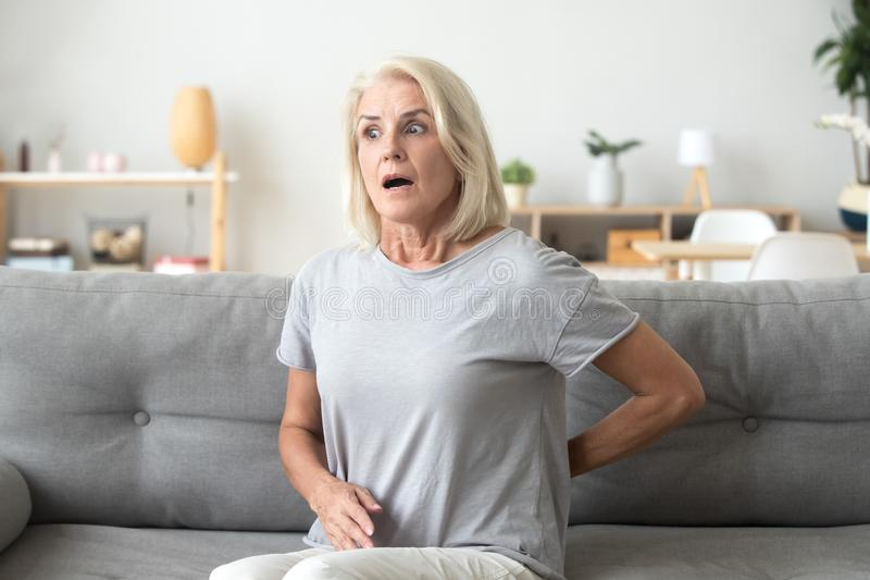 Mature woman sitting on couch suffers from back pain royalty free stock photography