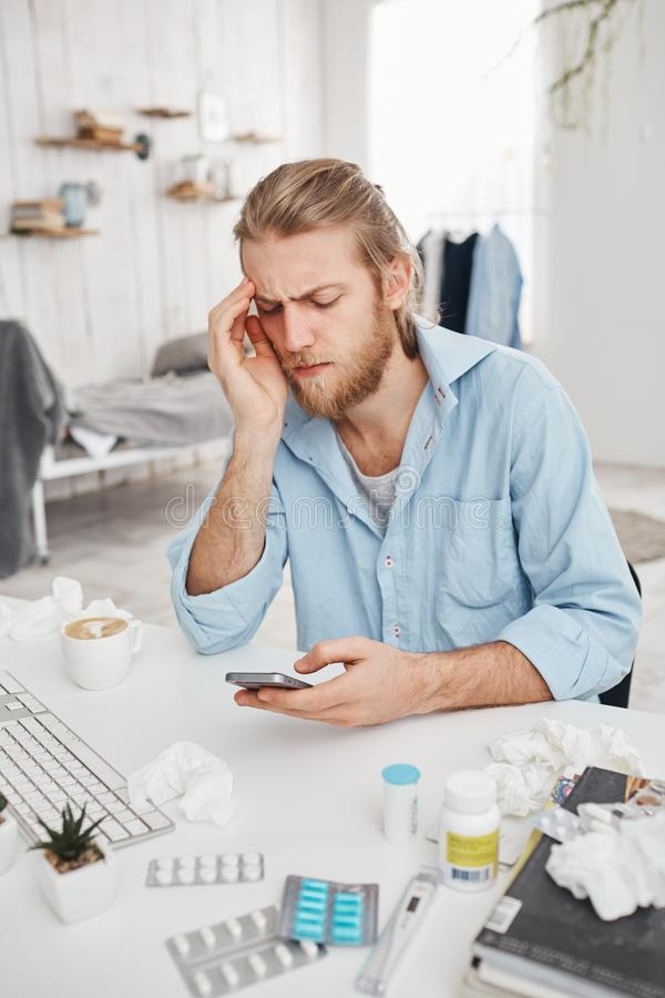 Unhappy bearded young male manager sitting at table surrounded by pills, tablets, drugs. Fair-haired office worker has stock image